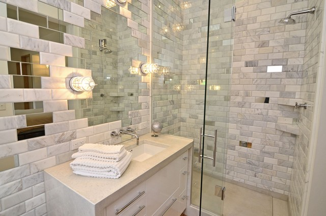 Modern bathroom with glass walk-in shower with carrara marble subway tile  shower surround, white vanity wrapped in stone paired with wall-mounted  faucet and ...