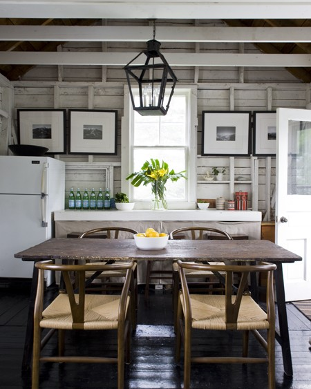 ... over salvaged wood dining table and Hans Wegner Wishbone Chairs