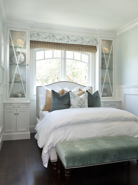 Cottage bedroom with glass-front cabinets flanking white camelback ...