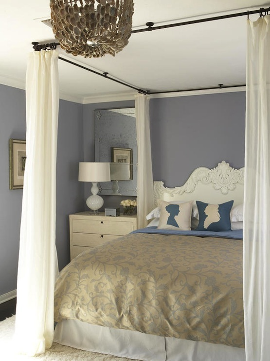 Chic bedroom with Oly Studio Jenny Chandelier over iron canopy bed created  with wrought iron rods suspended from ceiling, white rococo headboard, ...