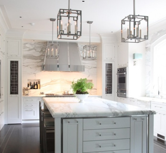 Two Tone Kitchen With Gray Kitchen Island, White Cabinets With Lucite  Pulls, Calcutta Marble Slab Countertops And Backsplash And Polished Nickel  Pendants.