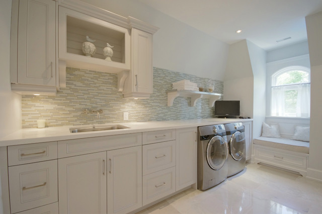 Contemporary laundry room with crisp white cabinets, white countertops,  blue and gray linear glass tile backsplash, silver front-load washer &  dryer and ...