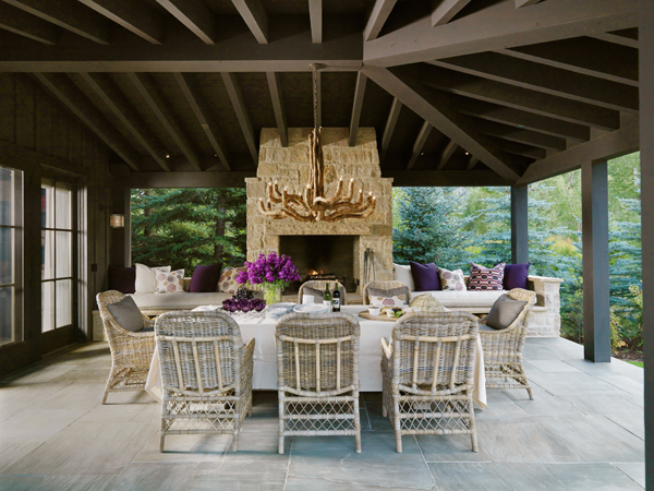 Covered Deck With Stone Fireplace Flanked By Built In Benches, Purple  Pillows And Wicker Chairs.