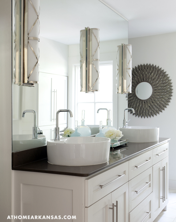 mirror over white double bathroom vanity with round vessel sinks, gray