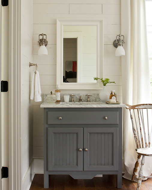 cottage bathroom with gray vanity with beadboard doors white carrara