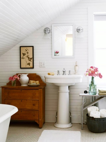 Cottage attic bathroom with sloped ceiling and white paneled walls  white  pedestal sink with white mirror  vintage cabinet  claw foot tub an vintage  penny. Attic Bathroom Sloped Ceiling Design Ideas
