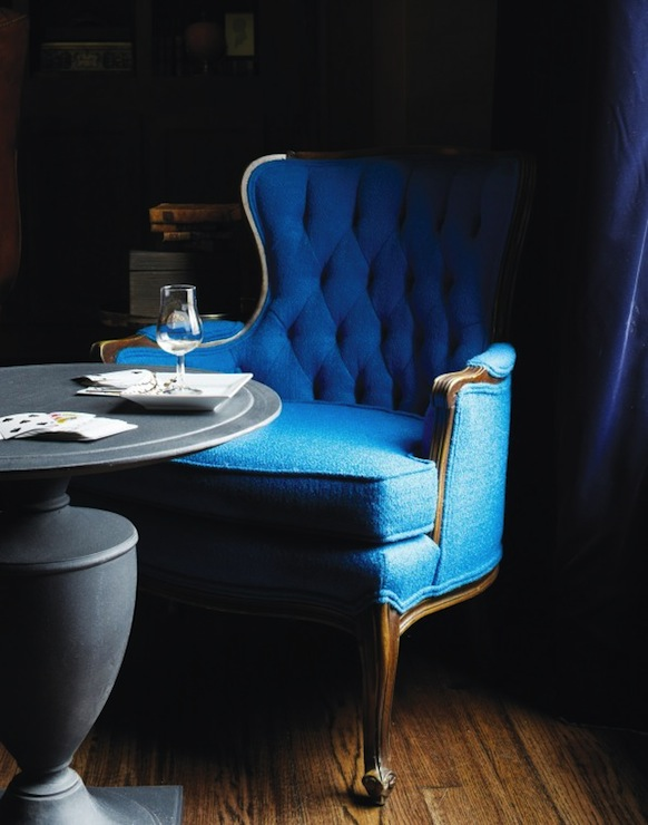 Peacock blue tufted Bergere Chair, zinc pedestal table and royal blue silk  curtains.