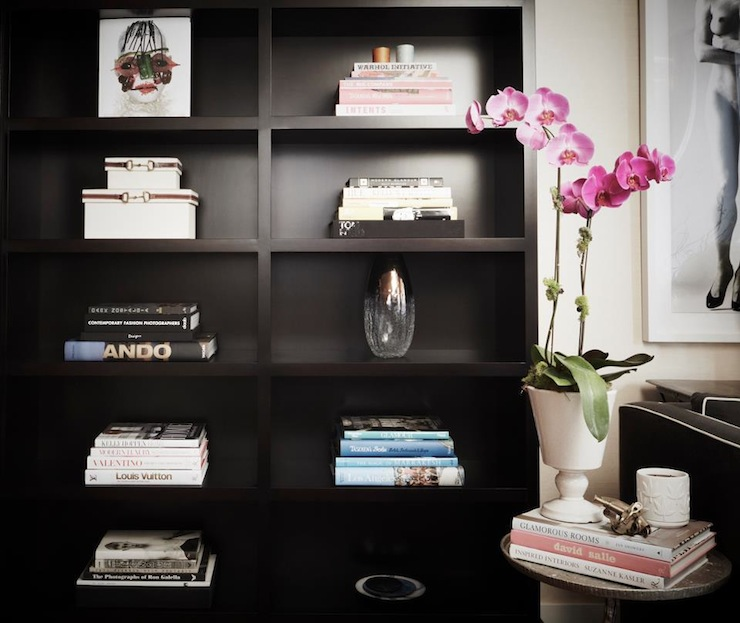 Chic Office With Styled Black Bookcase, Pink Orchid In White Pedestal Urn  Vase, Black Modern Sofa With White Piping And Black Marble Top Accent Table.