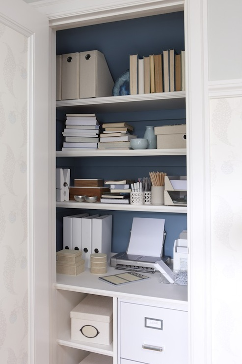 Closet desk with interiors walls painted blue, white floating shelves, file  cabinet, built-in desk and office supplies.