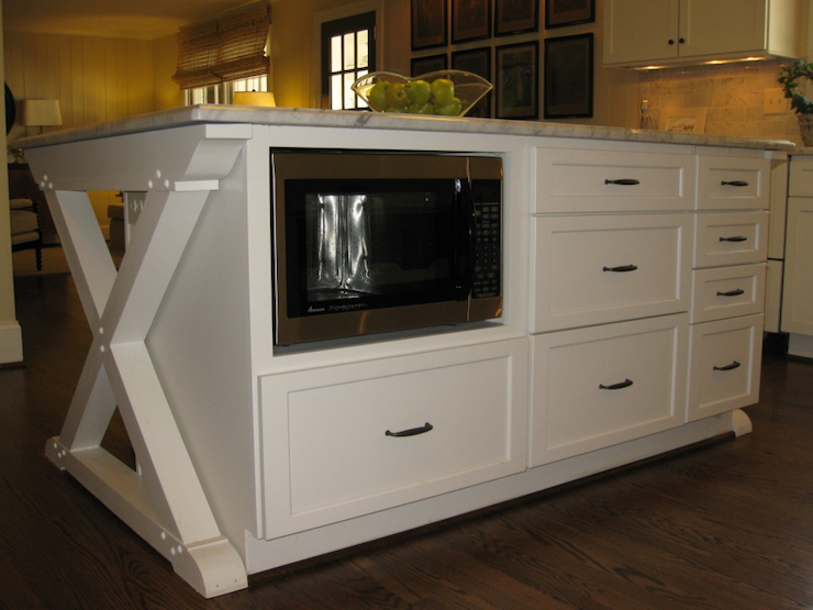 Creamy White Cabinets In X Base Kitchen Island With Built In Microwave Nook  And Marble Countertops.