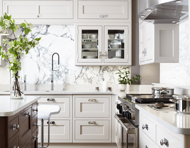 Two-tone kitchen with inset cream cabinets, cabinets over sink, chocolate  brown kitchen island, marble slab backsplash, white countertops, and white  Piston ...