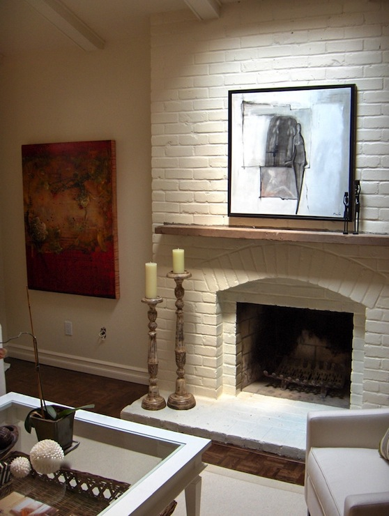 White brick fireplace with wooden mantle.