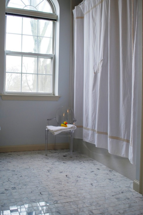 gorgeous bathroom with calcutta marble tile floor monogrammed shower curtain arched bathroom window pale blue walls paint color and louis ghost chair