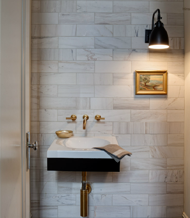 Beautiful Powder Room With Marble Subway Tile Backsplash And Modern Black  Bathroom Vanity With Gold Wall Mount Faucet With Lever Handles By Kohler.