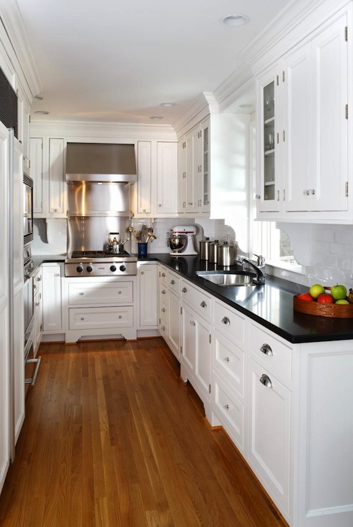 White kitchen cabinets with black countertops for Black and white galley kitchen