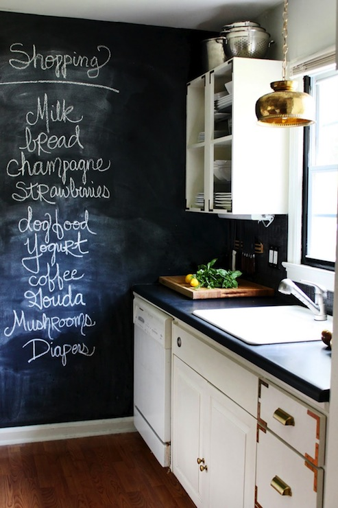 Incredible chalkboard wall in kitchen with white cabinetry with campaign  style details and drawer pulls.
