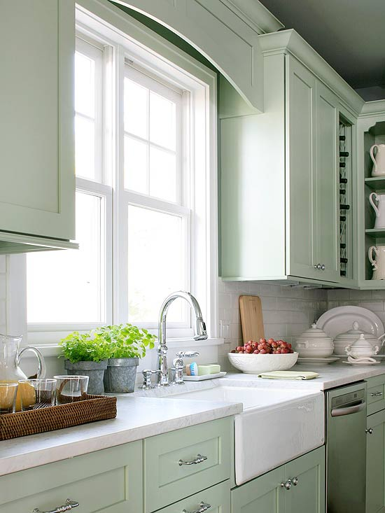 green kitchen with pale mint green cabinets and light stone