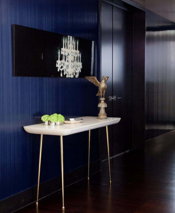 dramatic art deco foyer vignette featuring bold blue wall treatment and sleek chandelier art hanging over a midcentury marbletop console table holding