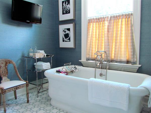 Splendid master bathroom with blue grasscloth covered walls and wall-mount  bathroom flatscreen TV.