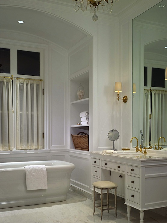 elegant white master bathroom with white wainscoted walls and arched