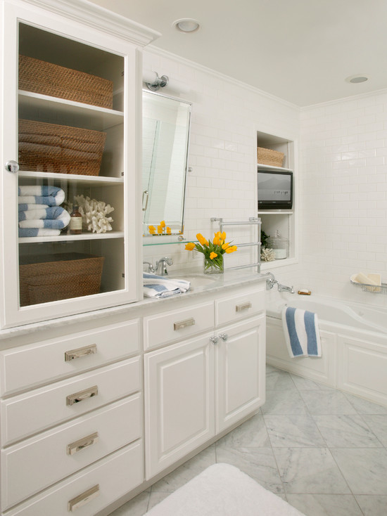 vanity with carrara marble countertops and glass fronted cabinet