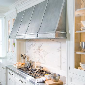cabinets paired with marble countertops and marble slab backsplash