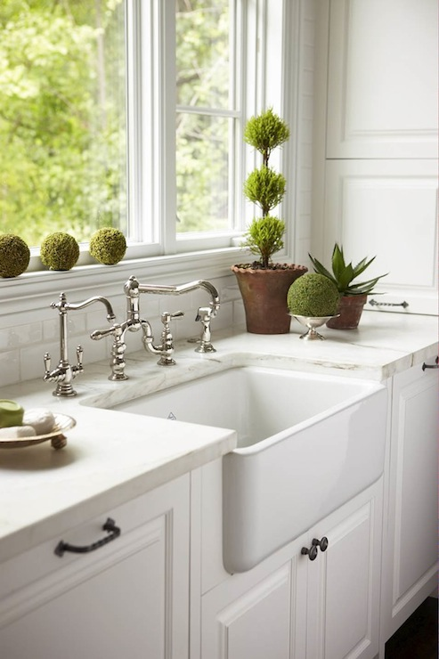 white kitchen with farmhouse sink with polished nickel vintage faucet flanked by white wood paneled dishwashers