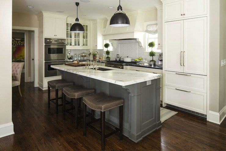 Two tone kitchen with white kitchen cabinets paired with black granite