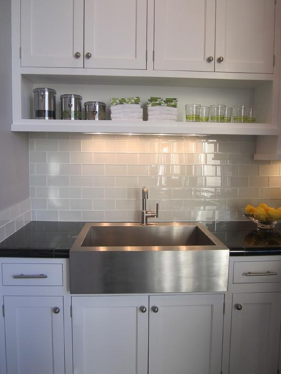 kitchen with white cabinets and glass backsplash stainless steel farm