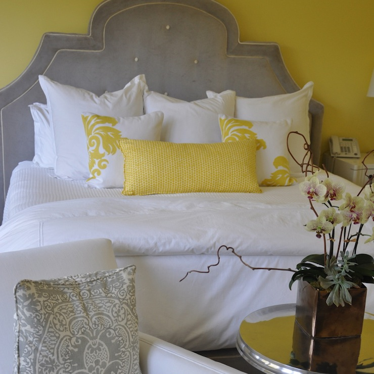 yellow and gray bedroom with yellow walls framing gray velvet tufted