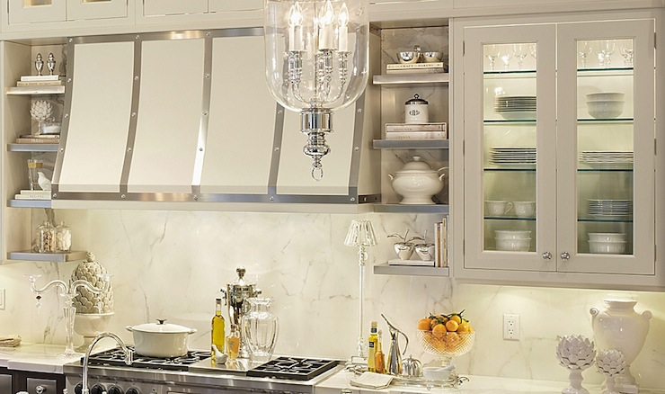 Glamorous kitchen design with glass-front kitchen cabinets paired with  calcutta marble countertops and calcutta marble slab backsplash. Downsview