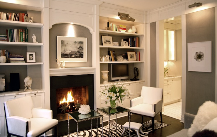 Gorgeous built-in bookshelves surrounding fireplace with sconce lighting.