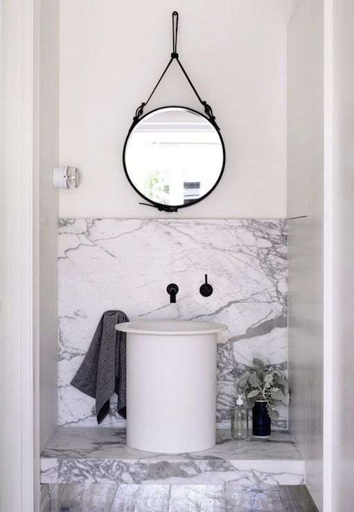 via Design Files - Amazing bathroom with black leather captain's mirror  hanging over white vessel sink with wall-mount oil-rubbed bronze faucet kit.