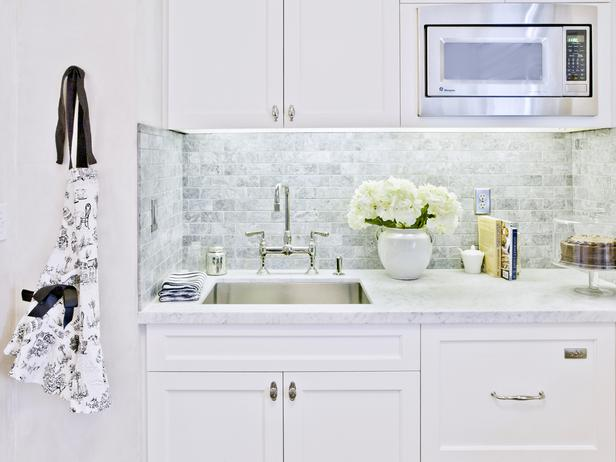 Fabulous Kitchen With Creamy White Shaker Cabinets With Marble Countertops  And Mini Marble Subway Tile Backsplash.