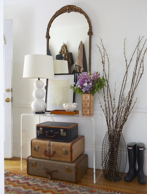 Incroyable Foyer With Stacked Vintage Suitcases Tucked Under CB2 Peekaboo Clear  Console Table Filled With White Triple Gourd Lamp, Orange Tray And White  And Orange ...