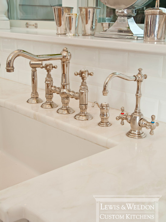 beautiful detail shot of undermount farmhouse sink with traditional style bridge faucet set with faucet hose builtin soap dispenser and purified water