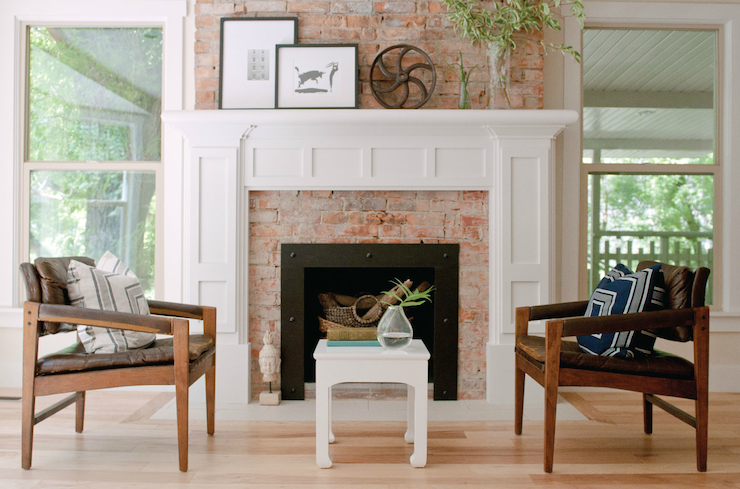Fireplace seating features brown leather mid-century modern chairs with geometric pillows and white chinoiserie table over light wood floors.
