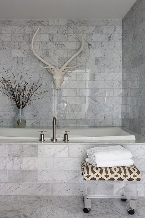Wonderful Luxurious Bathroom Features Lucite Ottoman With Kelly Wearstler Imperial  Trellis In Parchment/Midnight Cushion Over Carrara Marble Tiled Floor.