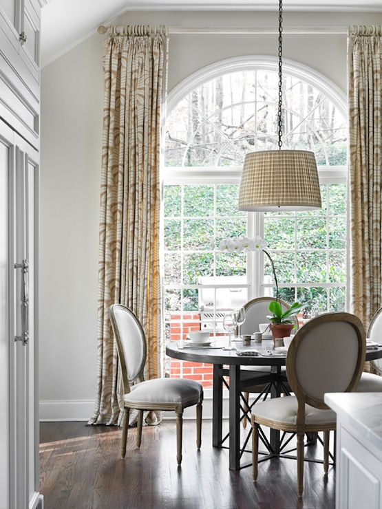 Elegant dining room with floor to ceiling cream patterned curtains covering  French doors and palladian window.
