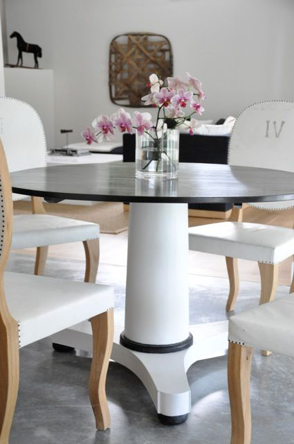 chic black and white dining room with black and white pedestal table surrounded by oval back white louis iv chairs