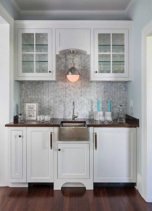 gorgeous wet bar with white shaker cabinetry and glass fronted upper cabinets