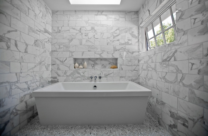 amazing marble bathroom with skylight over modern tub accented with marble subway tiled walls and white carrara marble hex tile floor - White Carrara Marble