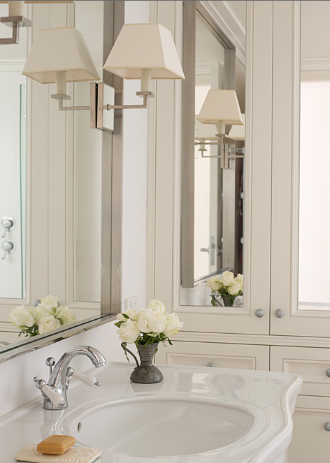 chic bathroom featuring mirrored cabinets as well as satin nickel