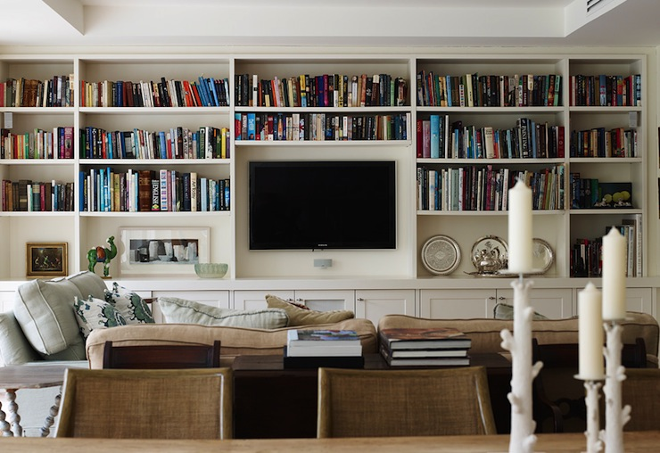amazing living room with wall of floor to ceiling built in bookcases