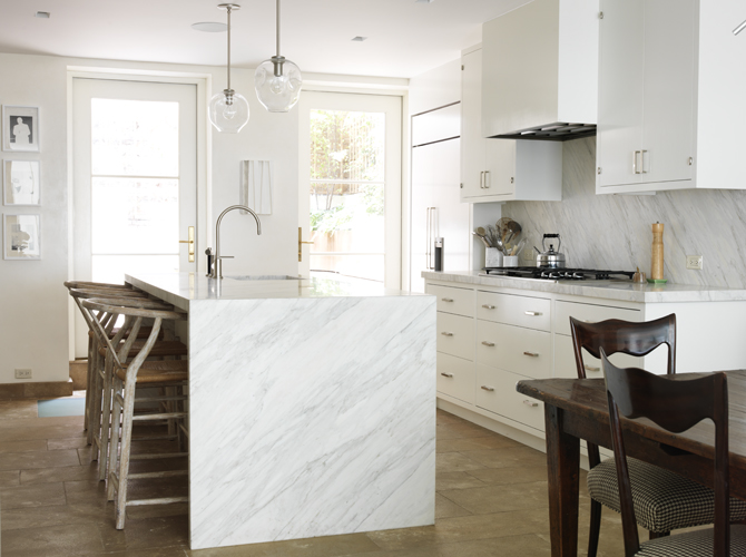Gorgeous sun filled kitchen with clear glass light pendants over white  marble waterfall kitchen island with sink accented with gooseneck faucet  lined with ...