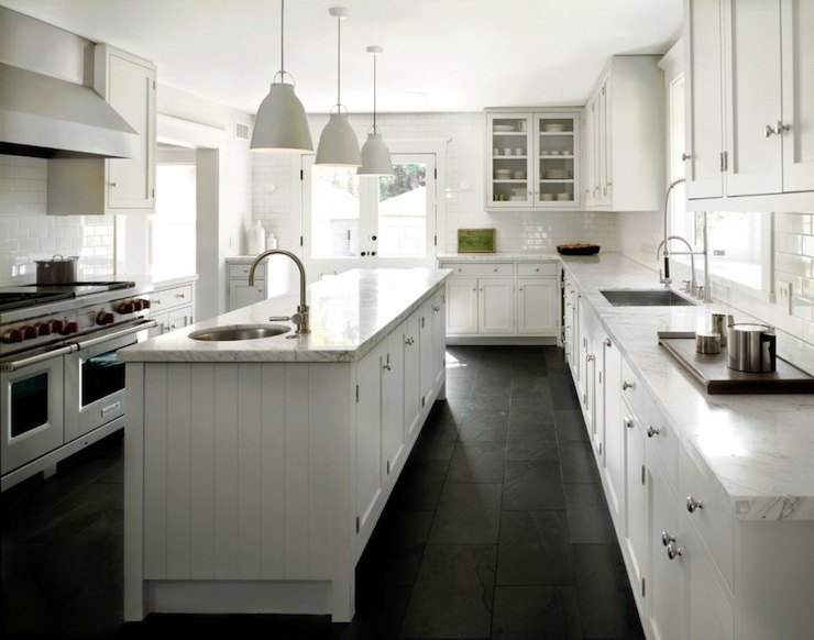 countertops and subway tile backsplash over black slate tiled floor
