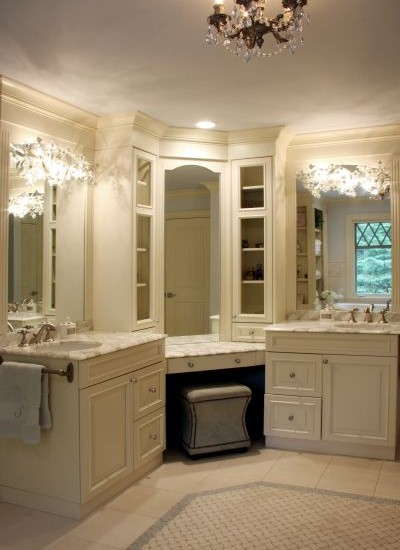 beautiful master bathroom design with gray vanity ottoman tucked under corner vanity accented with inset mirror and glass front cabinets flanked by his and