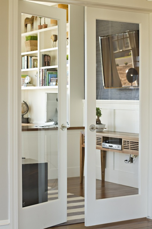 Fabulous Glass Paned Doors Lead To A Sunny Office With Hardwood Floors  Layered With A Gray And White Striped Area Rug.