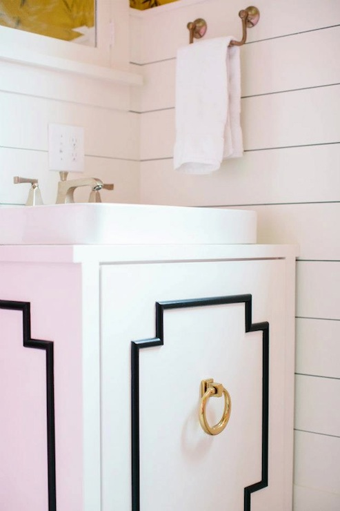 Chic Girlu0027s Bathroom With White Medicine Cabinet Over Black And White  Bathroom Vanity Accented With Brass Ring Pulls On White Wood Paneling.