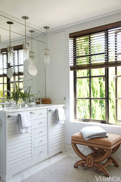 paul wiseman chic bathroom with cluster of white glass pendants over white louvered double vanity with white marble countertop and frameless mirror